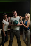 Friends Bowling Together. Group Of Three Friends In A Bowling Alley Having Fun, Two Of Them Cheering The One In Charge To Throw The Bowling Ball stock photo
