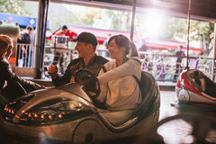 Friends on bumper car ride in amusement park Stock Photo