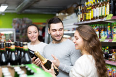 Friends buying champagne in supermarket Royalty Free Stock Photo