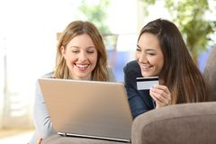 Friends buying online together at home. Front view portrait of two friends buying online together with a laptop and a credit card at home Stock Photo
