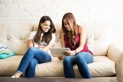 Friends buying stuff online. Cute female friends using a tablet computer and a credit card to buy some stuff online Royalty Free Stock Photography