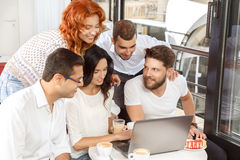 Friends in cafe with laptop. Friends gathered in a cafe on the weekend Royalty Free Stock Photos
