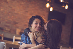 Friends in a cafe. Two girl friends meeting in a cafe, hugging and enjoying their time together Royalty Free Stock Photography