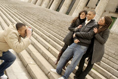 Friends with camera. Happy, hugging friends taking pictures on their digital camera Stock Images