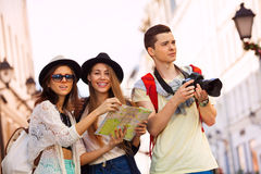 Friends with camera and city map as tourists Stock Images