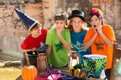 Friends at camp make faces. Friends in acting camp make silly faces while standing beside table with pumpkin and cauldron Royalty Free Stock Photography