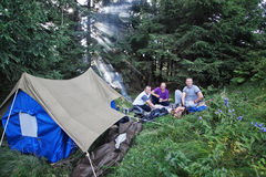 Friends in the campaign with a tent in the forest. Royalty Free Stock Photo