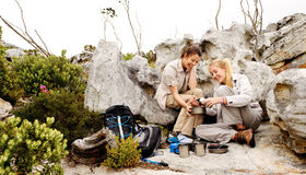Friends camping. Two girls open a can of baked beans while they are camping and hiking in the wilderness royalty free stock image