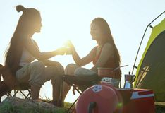 Friends camping eating food concept, Asian couple camping in their tent on the sunny day, Vacation Concept stock photography