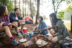Friends Camping Eating Food Concept. Friends camping eating food in the forest concept royalty free stock photography