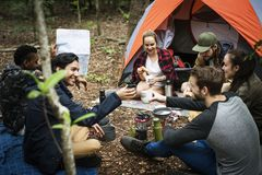 Friends camping in the forest together Stock Photography