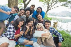 Friends camping selfie together. Group Of Friends Relaxing Outside Tents Camping and taking selfie Royalty Free Stock Photos