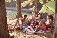 Friends on a camping trip relaxing on a blanket by a lake stock photography