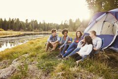 Friends on a camping trip relaxing by their tent near a lake royalty free stock photos