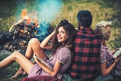 Friends camping in woods. Turn back guy looking at campfire while two girls lean on him. Smiling brunette girl with. Friends having picnic in woods. Turn back royalty free stock photo