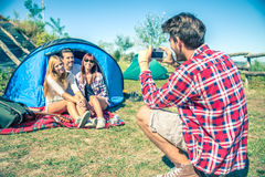 Friends in a campsite. Group of friends photographing themselves outside tent in a campsite - Young people resting on a excursion vacation royalty free stock image