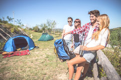 Friends in a campsite. Group of friends talking and having fun outside tent in a campsite - Young people resting on a excursion vacation in the nature stock images