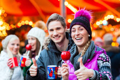 Friends with candy apple and eggnog on Christmas Market Royalty Free Stock Photography