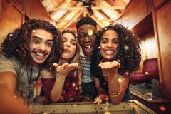 Friends capturing the fun in selfie at nightclub. Group of friends enjoying a party and blowing confetti. Men and women capturing the fun in selfie at nightclub royalty free stock photo