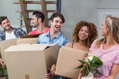 Friends carrying boxes while relocating in new house Royalty Free Stock Images