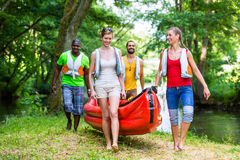 Friends carrying a canoe to river through forest. Happy friends carrying a canoe to forest river stock images