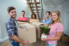 Friends carrying carton while relocating in new house Royalty Free Stock Photos