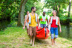 Friends carrying kayak or canoe to forest river. Happy friends carrying kayak or canoe to forest river royalty free stock images