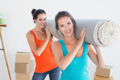 Friends carrying rolled rug after moving in a house Royalty Free Stock Image