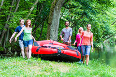 Friends carrying rubber boat to forest river Royalty Free Stock Images