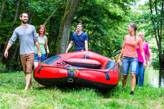 Friends carrying rubber boat to forest river stock photo