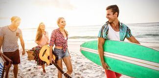 Friends carrying a surfboard and basket. At the beach royalty free illustration