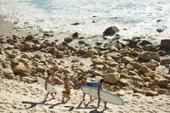 Friends Carrying Surfboards Along Beach Stock Photos
