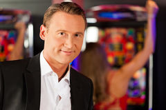 Friends in Casino on slot machine royalty free stock photography