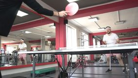 Friends caucasian man and beautiful pretty girl play table tennis in a modern gym, slow motion, lifestyle, competition stock footage