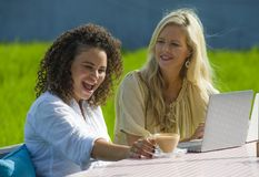 Friends caucasian woman and an afro mixed ethnicity girl enjoying together as digital nomad girlfriends working with laptop comput. Two happy female friends stock photos