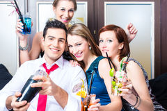 Friends celebrating with barkeeper in cocktail bar Stock Image
