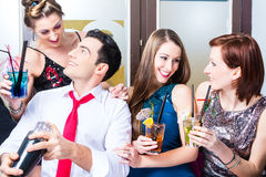 Friends celebrating with barkeeper in cocktail bar Royalty Free Stock Photos