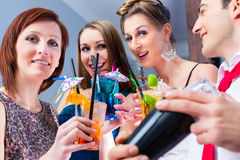 Friends celebrating with barkeeper in cocktail bar Royalty Free Stock Image