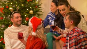 Friends celebrating christmas and drinking wine. Celebration and holidays concept - happy friends with glasses celebrating christmas at home party and drinking stock video footage