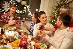 Friends celebrating christmas and drinking wine stock images