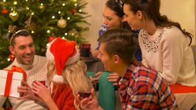 Friends celebrating christmas and giving presents. Celebration and holidays concept - happy friends with glasses celebrating christmas at home party, giving stock video