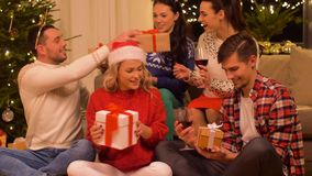 Friends celebrating christmas and giving presents stock video
