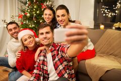 Friends celebrating christmas and taking selfie royalty free stock photography