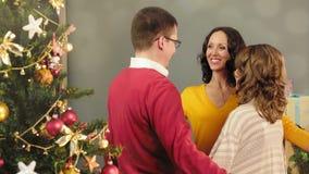 Friends celebrating New Year, embracing, congratulating near Christmas tree stock image