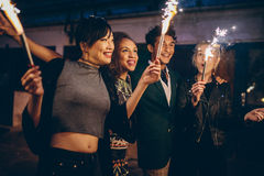 Friends celebrating new years eve with fireworks. Four young friends celebrating new years eve with fireworks. Group of people enjoying with sparklers on road in Royalty Free Stock Photos