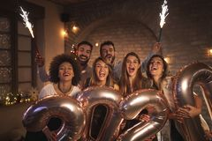 Free Friends Celebrating New Years Eve Waving With Sparklers And Holding 2020 Balloons Royalty Free Stock Photos - 164361808