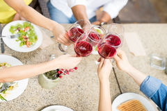 Friends celebrating with some wine. Top view of a group of five friends making a toast with wine while eating dinner together Royalty Free Stock Photo