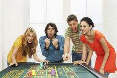 Friends Celebrating Win On Roulette Table. Group of multiethnic friends celebrating win on roulette table stock photo