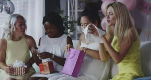 Friends celebrating young mother. Long shot of friends celebrating young mother with gifts stock video footage