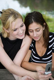 Friends on Cell Phone together (Beautiful Young Blonde and Brune Royalty Free Stock Photo